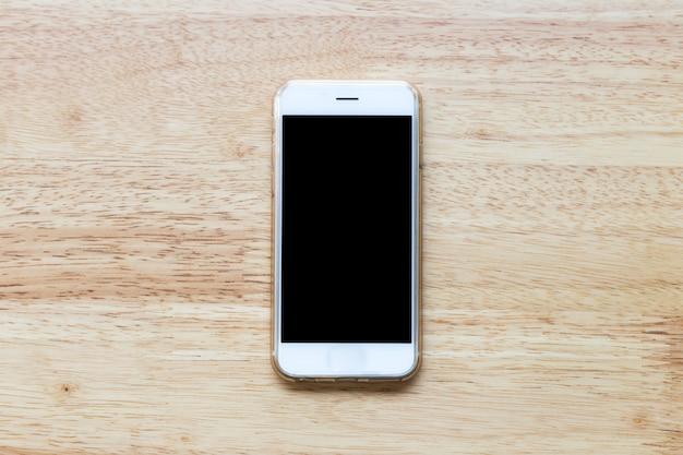 Telefono bianco mobile dello schermo in bianco sul fondo di legno della tavola.