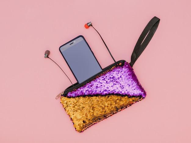 Telefono blu con cuffie colorate in una borsa colorata su un tavolo rosa