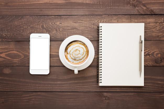 Telefono caffè e libro bianco sul tavolo in legno vista dall'alto