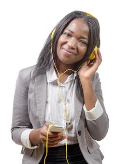 Telefono cellulare africano della tenuta della ragazza e ascoltare la musica