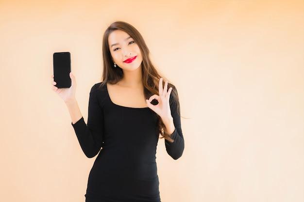 Telefono cellulare astuto di uso felice di bello giovane sorriso asiatico della donna del ritratto