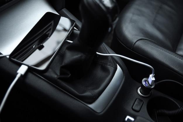 Telefono cellulare, batteria di ricarica per smartphone, ricarica nella presa per auto da vicino