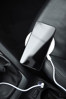 Telefono cellulare, batteria di ricarica per smartphone, ricarica wireless nella presa per auto da vicino