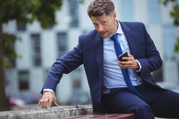Telefono cellulare bello della tenuta dell'uomo d'affari mentre per mezzo della compressa digitale