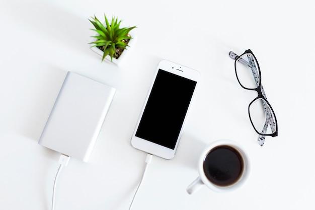 Telefono cellulare collegato con caricabatterie banca di potere con occhiali e tazza di caffè su sfondo bianco