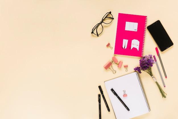Telefono cellulare con pennarelli; graffette di bulldog; occhiali e quaderni su fondo beige