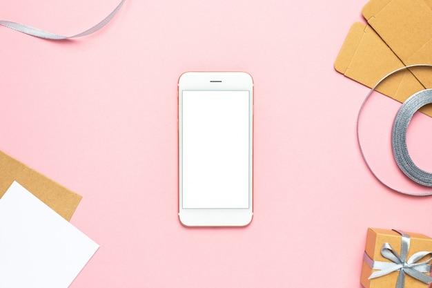 Telefono cellulare con regalo in composizione scatola per compleanno su sfondo rosa