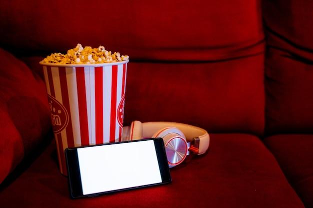 Telefono cellulare con schermo luminoso bianco vuoto con secchio di popcorn sul divano rosso