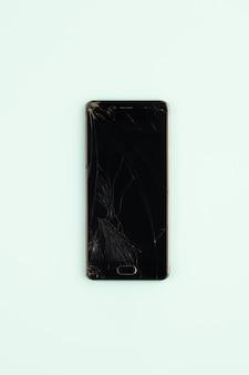Telefono cellulare con schermo nero rotto, vista dall'alto. smartphone danneggiato afflitto nel fondo verde pallido, colpo verticale