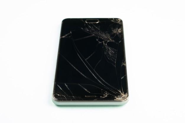 Telefono cellulare con schermo nero rotto, vista dall'alto. smartphone danneggiato in difficoltà in fondo verde pallido, profondità di campo