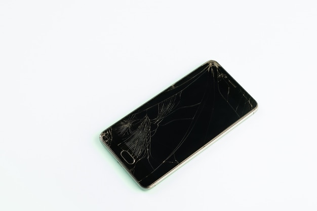 Telefono cellulare con schermo nero rotto, vista dall'alto. smartphone danneggiato in difficoltà in sfondo verde pallido
