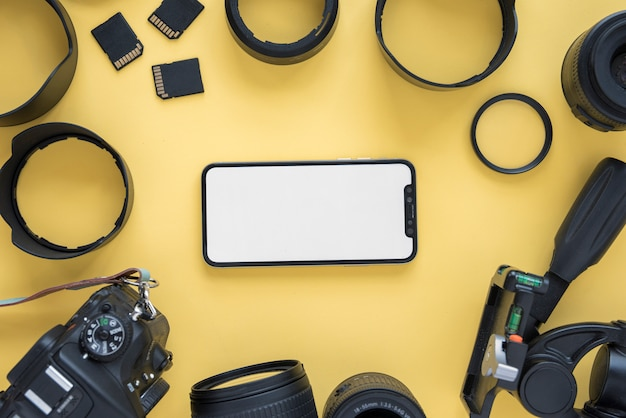 Telefono cellulare con schermo vuoto circondato da moderni accessori della fotocamera su sfondo giallo
