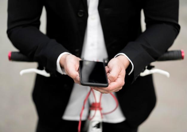 Telefono cellulare della tenuta del maschio adulto del primo piano