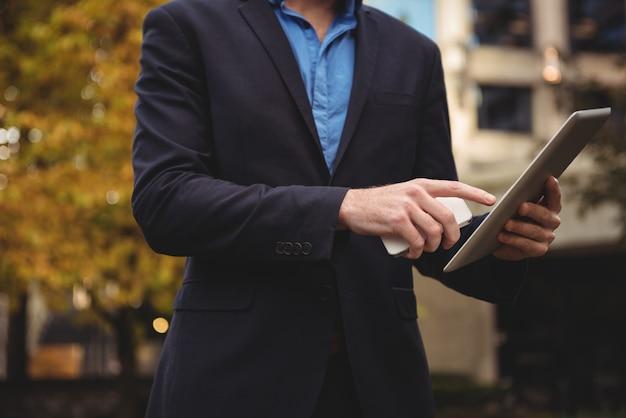Telefono cellulare della tenuta dell'uomo d'affari e compressa digitale usando