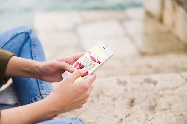 Telefono cellulare della tenuta della donna che mostra il buono di regalo sullo schermo