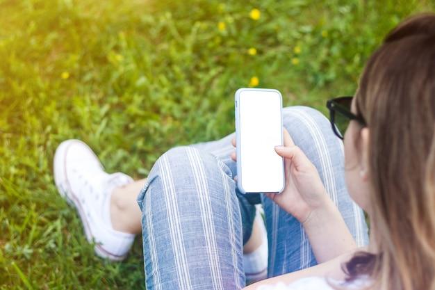 Telefono cellulare della tenuta della donna con lo schermo in bianco in sua mano. spazio in erba, raggi del sole.