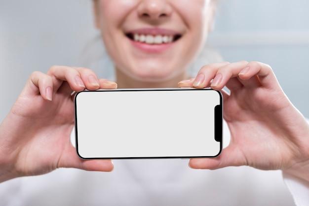 Telefono cellulare della tenuta della donna del primo piano