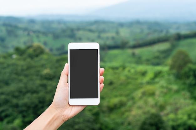 Telefono cellulare della tenuta della mano della donna sopra una montagna.
