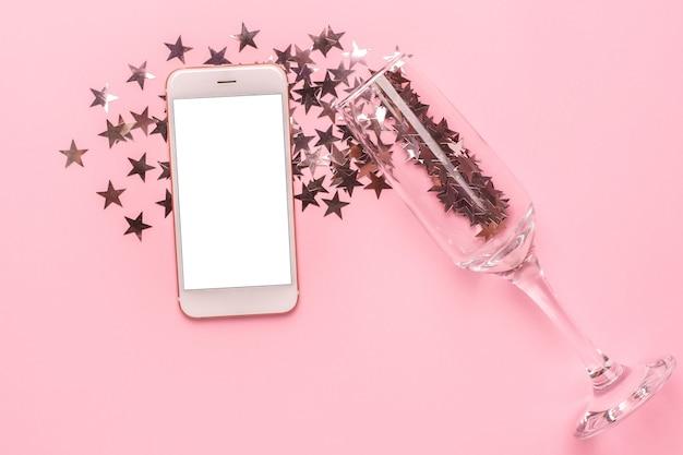 Telefono cellulare e bicchiere di champagne con stelle d'argento