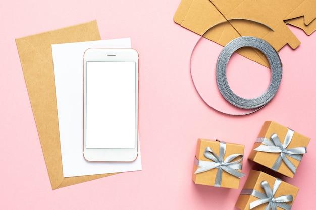 Telefono cellulare e carta bianca con il regalo in composizione nella scatola per il compleanno su fondo rosa