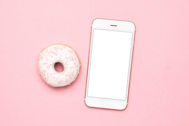 Telefono cellulare e ciambelle dolci alla fragola