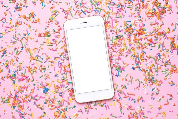 Telefono cellulare e dolce spruzza multicolore sul tavolo pastello rosa in stile piatto laico.