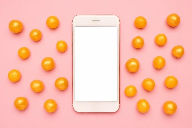 Telefono cellulare e dolci caramelle gialle su un rosa, tecnologia