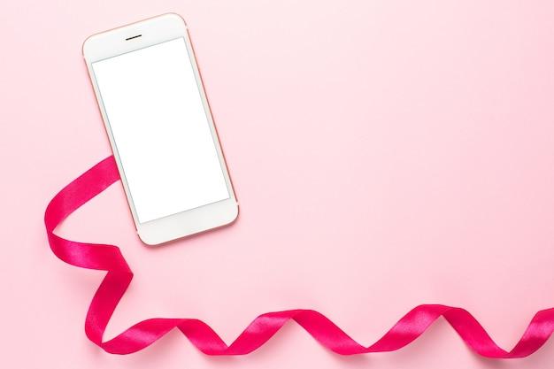 Telefono cellulare e nastro regalo sul rosa