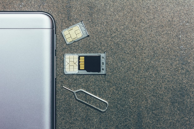 Telefono cellulare e slot aperti per nano sim card, micro sd drive e chiave in metallo su grigio con copyspace