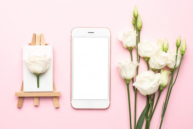 Telefono cellulare e tela per pittura con fiore bianco su rosa