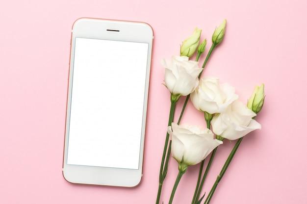 Telefono cellulare, fiore bianco e taccuino sul rosa