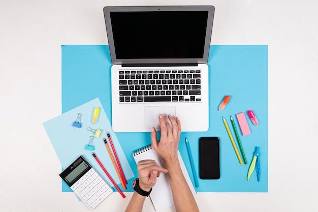 Telefono cellulare in mani, computer portatile, articoli di cancelleria isolati su bianco e blu