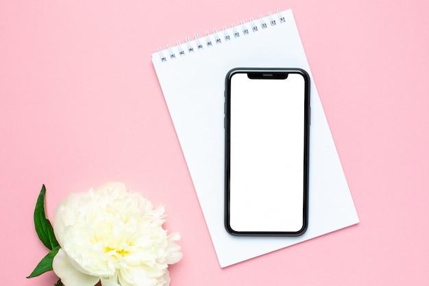 Telefono cellulare mock up, notebook e fiore di peonia sul tavolo pastello rosa. scrivania da lavoro donna. colore estivo