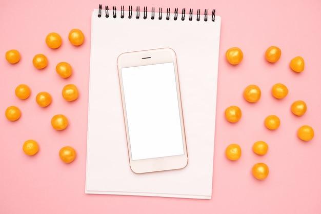 Telefono cellulare, notebook e caramelle su una rosa