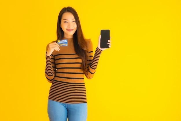 Telefono cellulare o cellulare astuto di bello giovane uso asiatico della donna del ritratto con la carta di credito per acquisto online