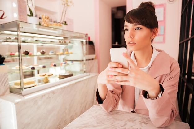 Telefono cellulare premuroso della tenuta della giovane donna