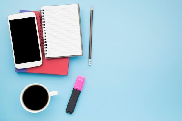 Telefono cellulare rosso della copertura del taccuino su stile pastello del fondo blu
