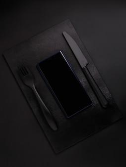 Telefono cellulare sul bordo nero con forchetta nera e coltello nero su sfondo nero, vista dall'alto