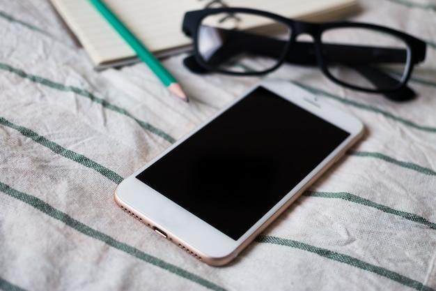 Telefono cellulare, taccuino, occhiali e matita