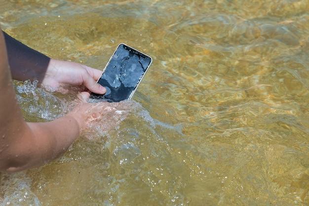 Telefono cellulare touch in una spiaggia e acqua