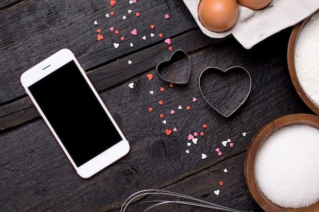 Telefono cellulare, utensili da cucina e cuori su legno