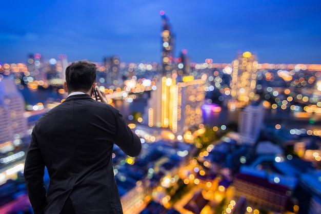 Telefono chiamante dell'uomo d'affari sopra la torre con il fondo della città di notte