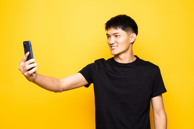 Telefono cinese asiatico della tenuta dell'uomo sopra la parete gialla isolata
