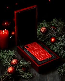 Telefono del presente del nuovo anno nella vista laterale della scatola rossa
