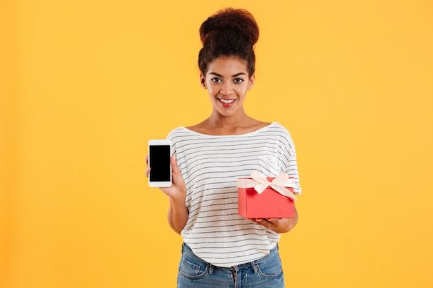 Telefono della tenuta della giovane signora con lo schermo e il presente in bianco