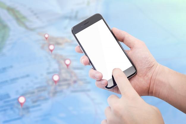 Telefono della tenuta della mano con lo schermo bianco vuoto sulla composizione nella mappa nell'icona dei gps e del giappone confusa