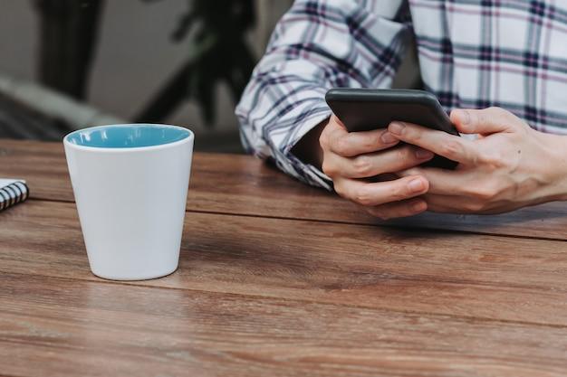 Telefono della tenuta della mano della donna sulla tavola di legno alla caffetteria