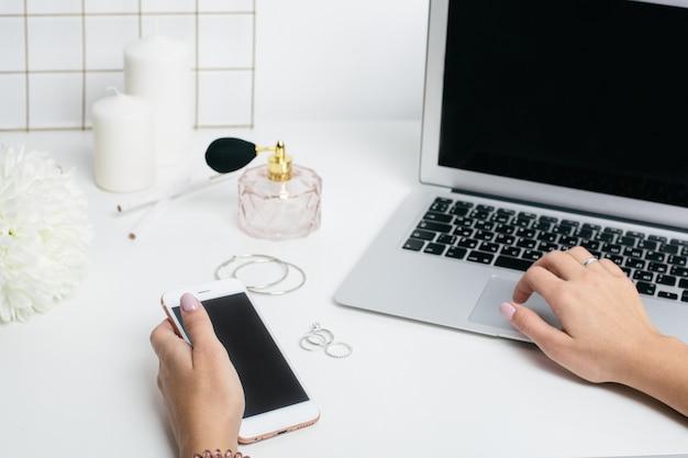 Telefono dello schermo in bianco in mano delle donne e tastiera del computer portatile sulla tavola bianca dell'ufficio