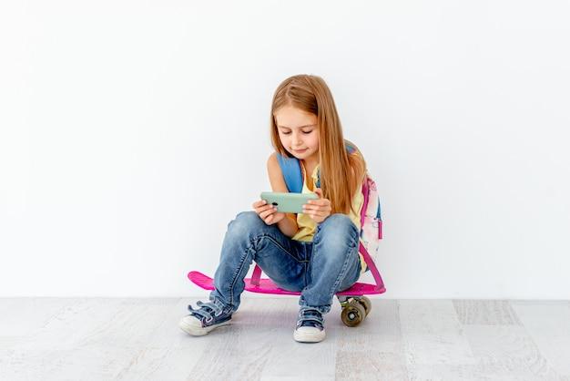 Telefono di sorveglianza della bambina, sedentesi sul pattino