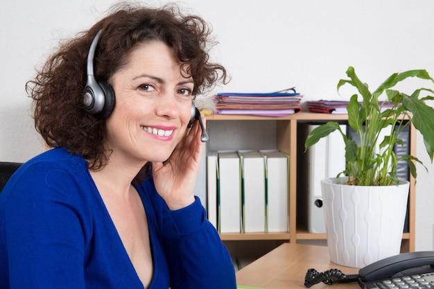 Telefono di supporto allegro sorridente in cuffia avricolare all'ufficio